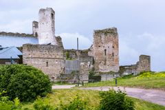 Ruins of an old castle. The ruins of an old fortress against a gray sky with a rocky road leading to it stock images
