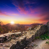Ruins of an old castle in the mountains in evening. Stone wall of an old ruined castle in the mountains Stock Image