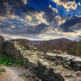 Ruins of an old castle in the mountains. Stone wall of an old ruined castle in the mountains Stock Photo