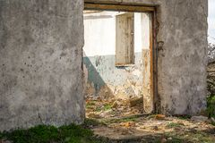 The ruins of an old earthen house without a roof. Holes in the wall at the site of windows and doors royalty free stock image