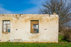 The ruins of an old earthen house without a roof. Holes in the wall at the site of windows and doors.  stock photography