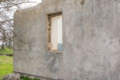 The ruins of an old earthen house without a roof. Holes in the wall at the site of windows and doors.  royalty free stock images