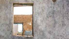 The ruins of an old earthen house without a roof. Holes in the wall at the site of windows and doors royalty free stock images