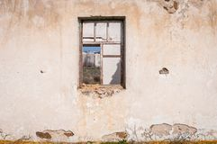 The ruins of an old earthen house without a roof. Holes in the wall at the site of windows and doors.  stock image