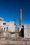 Ruins of an old factory with a chimney Royalty Free Stock Images