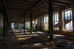 The ruins of the old factory. The light penetrating through the broken glass into the room of the destroyed plant Stock Images