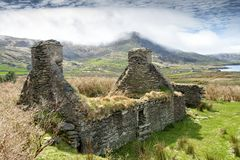Abandoned Farmhouse Overlooking Atlantic Ocean. Ruins of an old farm abandoned during the Irish Famine near Waterville on the Ring of Kerry. Local legend has it stock photography