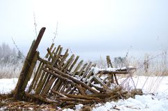 Slanting ruins of an old rotten village fence. Ruins of the old fence in a field Stock Photos
