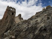The ruins of an old fortress on top of a rock cliff under a blue sky with white clouds, Tibet, the Himalayas, Northern India. Ruins of an old fortress on top of Royalty Free Stock Image