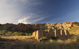 Ruins of old house with a mountain and clouds in the background Royalty Free Stock Images