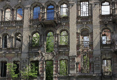 The ruins of the old houses. In the centre of the modern city. Right through the holes are visible blue window of a modern building.The ruins are waiting for Royalty Free Stock Images