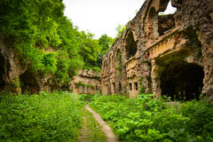 The ruins of the old military fort conquered by nature. Empty passes are long abandoned by people. Brick ruines from time Trees are hanging from above Stock Photography