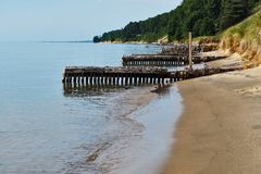 Sandy Shoreline & Old Piers on Lake Michigan Beach. royalty free stock photo