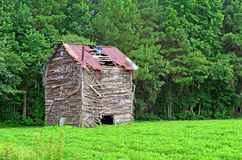 Ruins of Old Wooden Barn on Farmland. Ruins of an old wooden barn with rusting tin roof sitting on farmland next to the edge of the woods Stock Photography