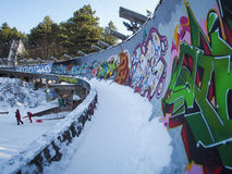 Ruins of Olympic bobsled track in Sarajevo with kids sledding Royalty Free Stock Photography