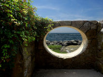 Ruins overlooking the ocean. An oval window in a stone wall looks out on a tide pool and the ocean Stock Images