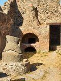 Ruins of Pompeii, ancient Roman city. Pompei, Campania. Italy. Roman oven and stone hand mill & x28;mola asinaria& x29; of a bakery of archaeological remains at Stock Photos