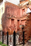 Ruins of red brick building walls. Wall of an old house, a metal rusty fence Stock Photos