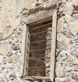 The ruins, the ruins of the destroyed castle fortress wall with a window with iron bars. Royalty Free Stock Images