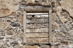 The ruins, the ruins of the destroyed castle fortress wall with a window with iron bars. Stock Photos