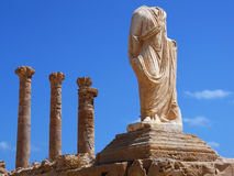 Ruins of Sabratha, Libya - Colonnade and Statue. A spectacular colonnade and a decapitated statue in front of Mediterranean Sea in the archaeological site of Royalty Free Stock Photos