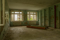 The ruins of the sanatorium. Gym. Plaster crumbles from the walls. Sporting ladder lying on the floor. Windows shattered . Debris and dirt on the floor Royalty Free Stock Photos