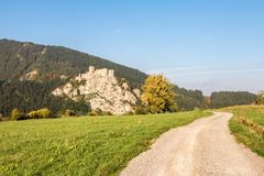 Ruins of Strecno castle in autumn landscape with dirt road Stock Image