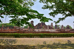 Ruins of stupa and statue of Buddha in Wat Mahathat, the ancient Thai temple in Ayutthaya Historical Park. Royalty Free Stock Photo