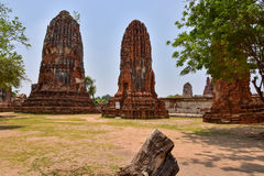 Ruins of stupa and statue of Buddha in Wat Mahathat, the ancient Thai temple in Ayutthaya Historical Park. Royalty Free Stock Image