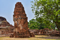 Ruins of stupa and statue of Buddha in Wat Mahathat, the ancient Thai temple in Ayutthaya Historical Park. Stock Photo