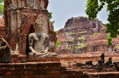 Ruins of stupa and statue of Buddha in Wat Mahathat, the ancient Thai temple in Ayutthaya Historical Park. Royalty Free Stock Photos