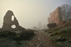 Ruins of the Viljandi Order Castle in misty morning. Ruins of the Viljandi Order Castle. Misty morning, cobble stone road in foreground, light gray sky as stock image