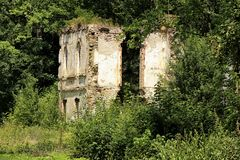 Ruins and walls of broken castle in bushes. Scrubby ruins and wall of broken border castle stock image