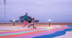 The ruins of West Pier, Brighton, East Sussex, UK. In the foreground, children playing and pavement painted in rainbow stripes. The ruins of West Pier, Brighton royalty free stock images
