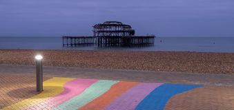 The ruins of West Pier, Brighton, East Sussex, UK. In the foreground, pebble beach and pavement painted in rainbow stripes. Photographed at dusk on a cold stock photography
