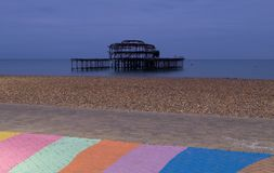 The ruins of West Pier, Brighton, East Sussex, UK. In the foreground, pebble beach and pavement painted in rainbow stripes. Photographed at dusk on a cold royalty free stock photo