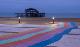 The ruins of West Pier, Brighton, East Sussex, UK. In the foreground, pebble beach and pavement painted in rainbow stripes. Photographed at dusk on a cold stock photos
