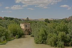 Remains of an old watermill in Guadalquivir river near Cordoba. Ruinss of an old water mill between trees on an island in Guadalquivir river near Cordoba stock photos