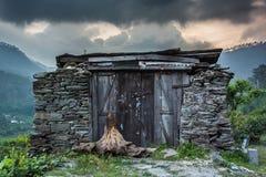 Ruiny dom w górach z chmurami i górach w tle przy półmrokiem zdjęcia royalty free
