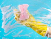 Ruit van het hand de schoonmakende glas met detergens Stock Afbeelding