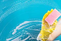 Ruit van het hand de schoonmakende glas met detergens Royalty-vrije Stock Foto's