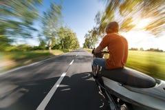 Ruiter op autopedmotorfiets in brede rijweg met mooi aangelegd landschap Stock Afbeeldingen