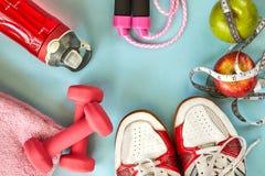ruits、哑铃、水瓶、绳索、运动鞋和米在蓝色背景 免版税库存图片