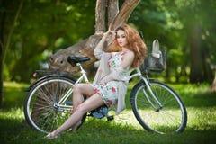 Ruivo bonito que relaxa com a bicicleta no parque do verão foto de stock