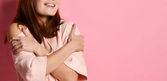 Ruivo fêmea no equipamento moderno, abraçando-se ao estar com os olhos fechados sobre a parede cinzenta fotos de stock royalty free