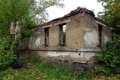 Rujnujący cegła dom w zupełnym desolation wśród jesieni drzew obraz stock