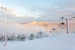 Ruka,芬兰- 2012年11月28日:滑雪者坐椅子滑雪电缆车在Ruka滑雪场在结冰的天 免版税库存图片