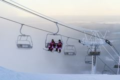 Ruka, Finland - November 27, 2012: Skiers are sitting on the chair ski lift at Ruka ski resort in freezing day stock photo