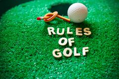 Rule of golf. Rules of golf on green course next to hole Royalty Free Stock Photo