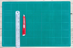 A ruler and cutter on green cutting mat Royalty Free Stock Image